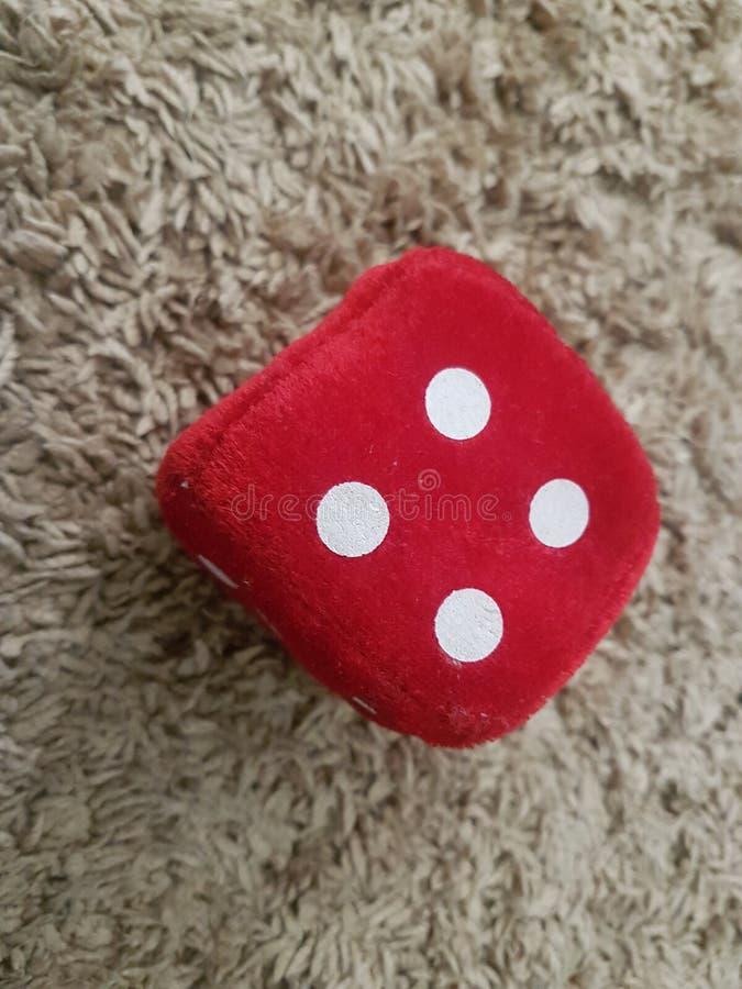 Czerwone Aksamitne kostki do gry z liczb? cztery bawi? si? zdjęcia stock