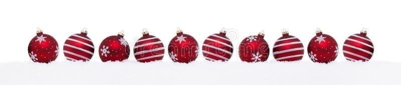 Czerwone boże narodzenie piłki odizolowywać na śniegu z rzędu obrazy royalty free