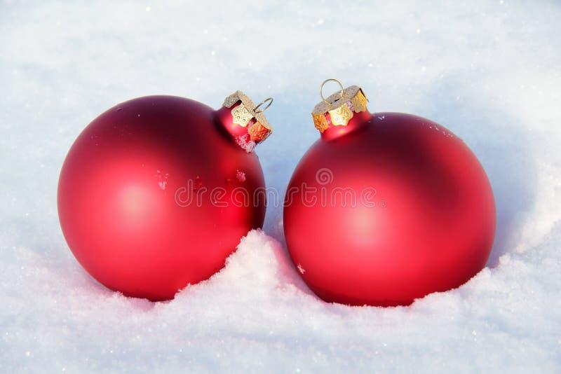 Czerwone Bożenarodzeniowe piłki w śniegu obrazy stock