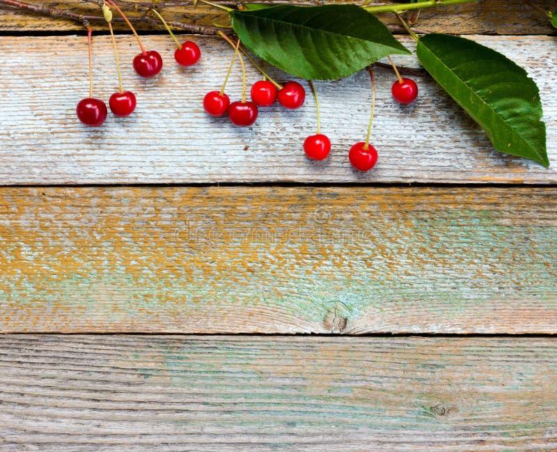 Czerwone dojrzałe wiśnie na tle stara stajnia wsiadają fotografia stock