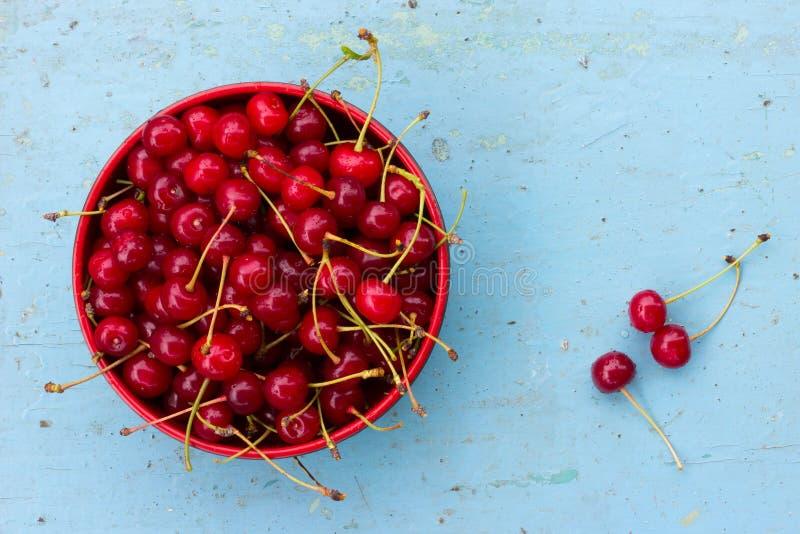 Czerwone dojrzałe wiśnie z ogonami w kurenda talerzu na starym błękitnym drewnianym tle zdjęcie stock