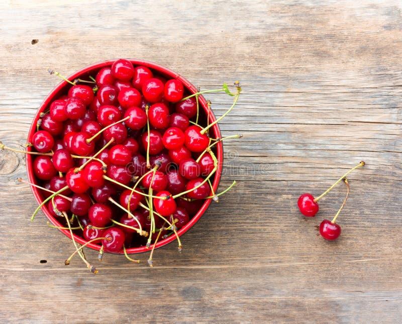 Czerwone dojrzałe wiśnie z ogonami w kurenda talerzu na starym drewnianym tle zdjęcia stock