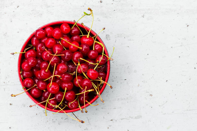 Czerwone dojrzałe wiśnie z ogonami w kurenda talerzu na starym szarym drewnianym tle z przestrzenią dla teksta obrazy stock
