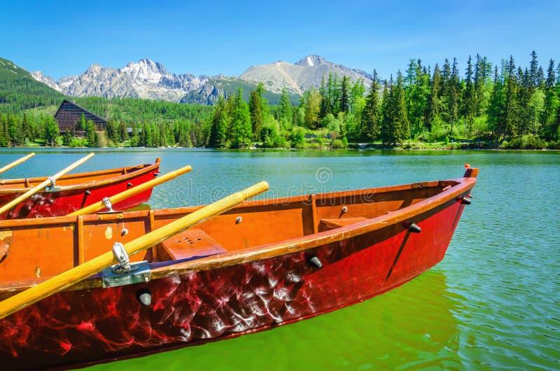 Czerwone drewniane łodzie na halnym jeziornym Strbske Pleso fotografia stock