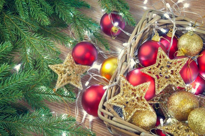 Czerwone i złote Bożenarodzeniowe dekoracje bawją się piłki i grają główna rolę tło z girlandą światła obraz royalty free