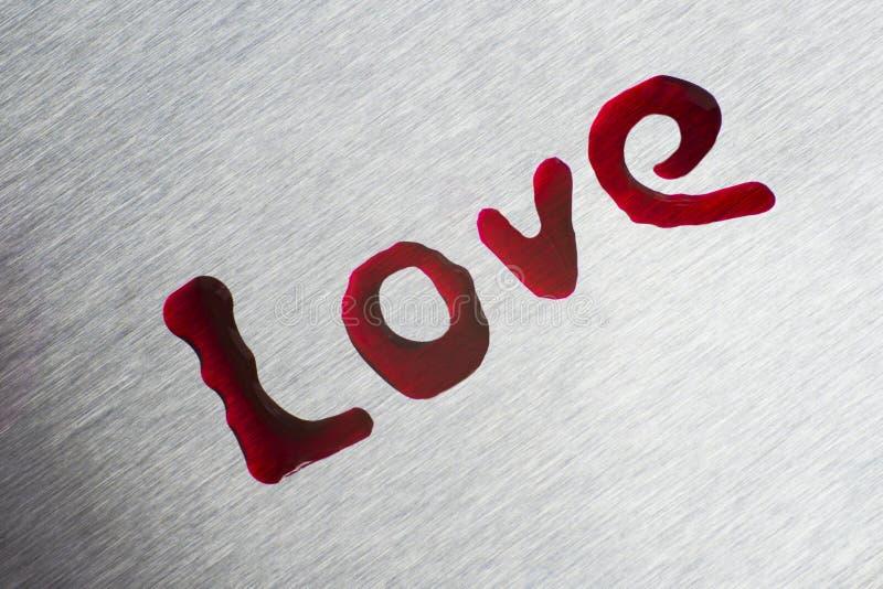 Czerwone krople w formie słowo miłości Powierzchnia jest kruszcowa zdjęcia royalty free