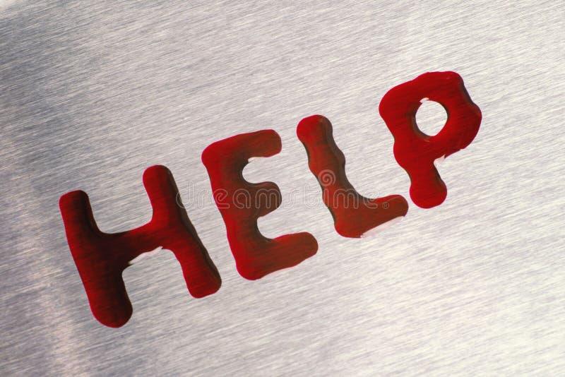 Czerwone krople w postaci słowo pomocy Powierzchnia jest kruszcowa zdjęcie stock