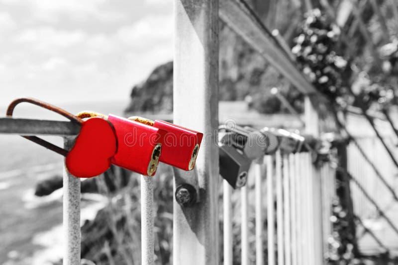 Czerwone miłość kłódki przy Riomaggiore wioską Cinque Terre Włochy - czarny i biały fotografia obraz stock