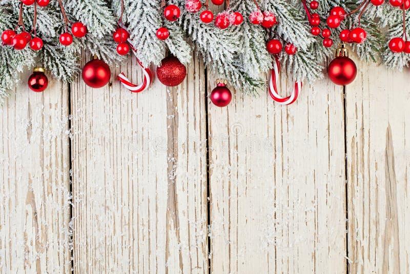 Czerwone mrożone jagody, bąbelki i zielona gałąź na białym drewnianym tle Granica świąteczna Minimalny płaski element Xmas obrazy royalty free