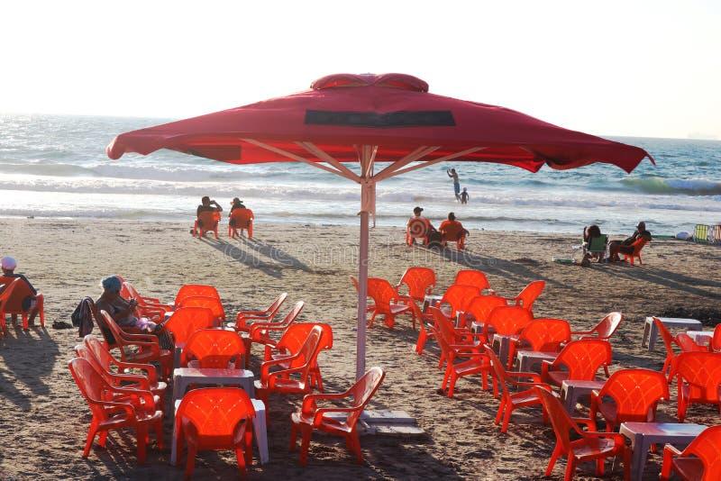 Czerwone parasol i pomarańczowe krzesła na plaży obraz stock