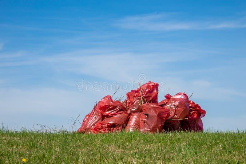 Czerwone plastikowe grat torby pełno śmieci zdjęcia stock