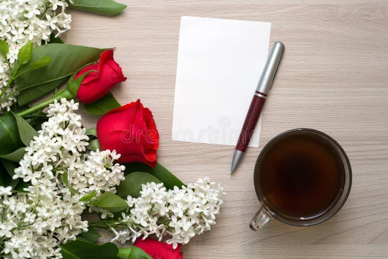 Czerwone róże, bzy, notepad i pióro na stole, zdjęcie royalty free