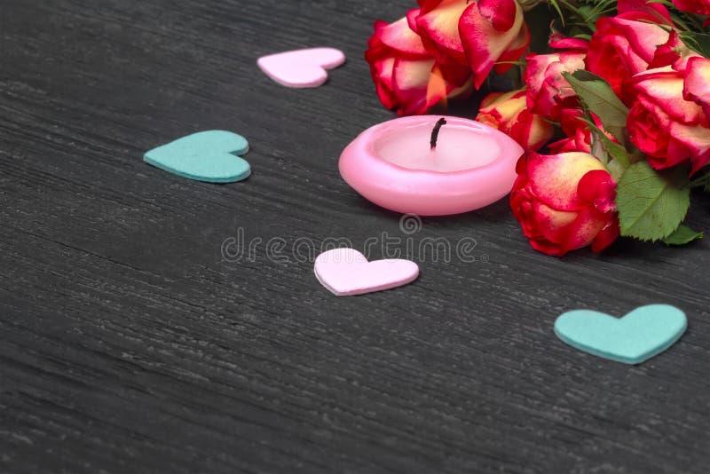 Czerwone róże i świeczka na drewnianym tle obraz royalty free