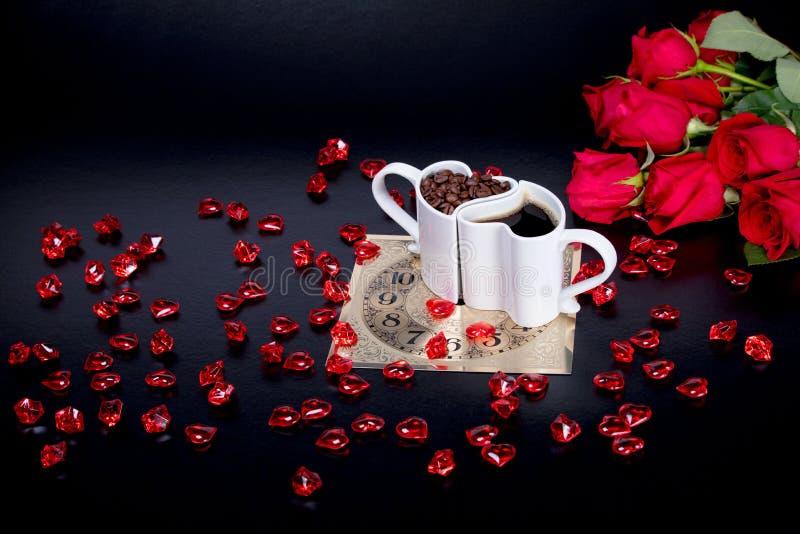 Czerwone róże i czerwoni szklani serca obok serca kształtowali kawowych kubki zdjęcie royalty free