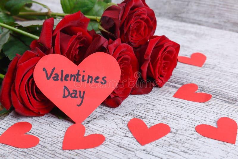 Czerwone róże na szarym drewnianym tle z sercem z inskrypcją dzień St walentynka zdjęcie stock
