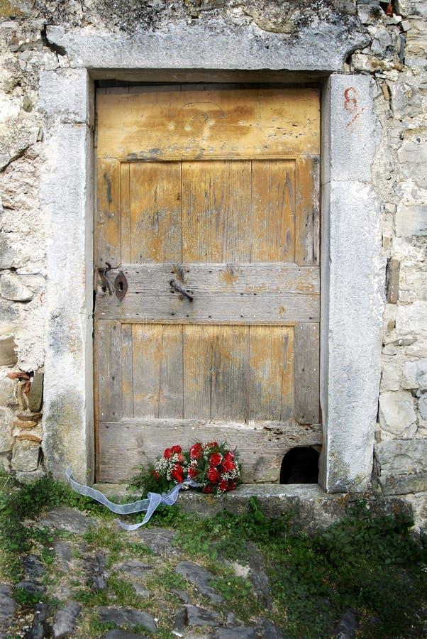 Czerwone róże poślubia bukiet i starego drewnianego drzwi obrazy royalty free