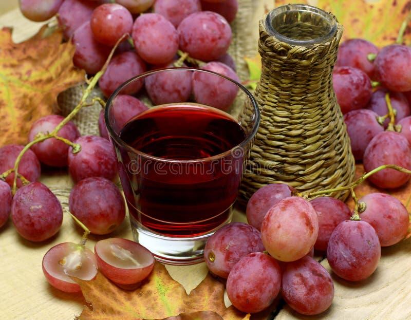 Czerwone wina domowej roboty łozinowa butelka i winogrona obrazy stock
