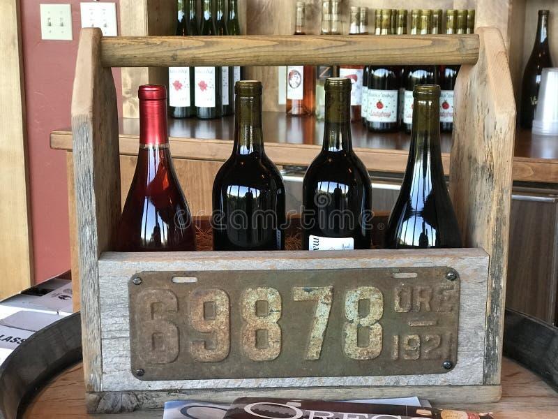 Czerwone wina na pokazie w drewnianym przewoźniku przy oceny grani wytwórnią win zdjęcia stock