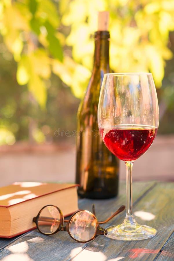 Czerwone wino i czerwieni książka obraz stock