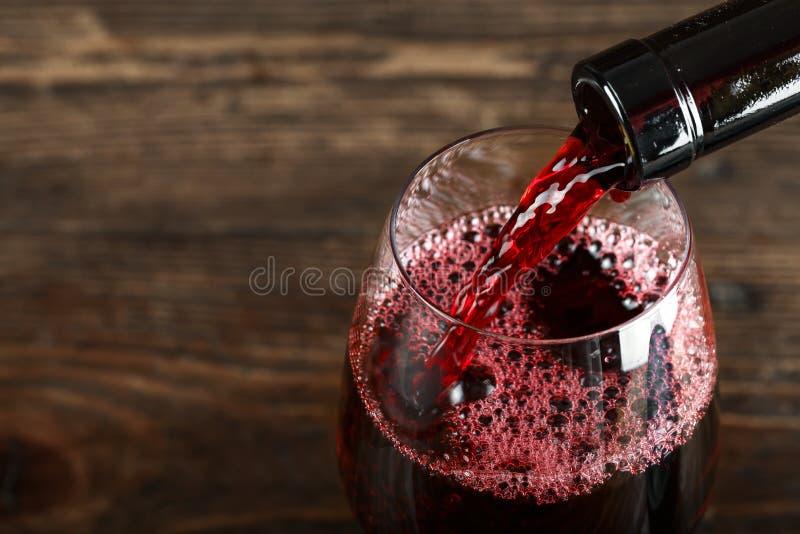 Czerwone wino nalewa od butelki obraz stock
