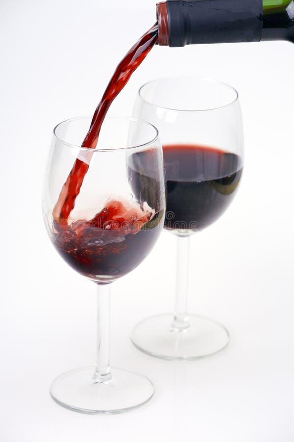 Czerwone wino nalewa w dwa szkła zdjęcie stock