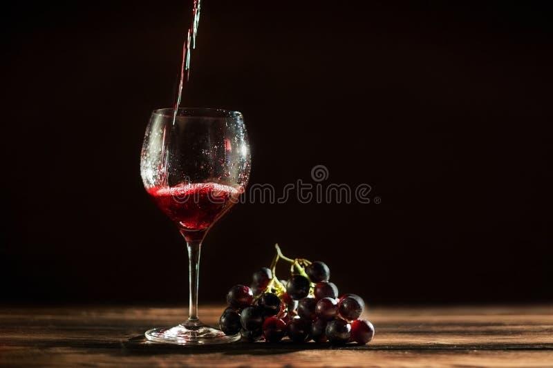 Czerwone wino nalewa w wysokiego dużego szkło na ciemnym tle Szkło z kroplami czerwone wino i wiązka winogrona zdjęcie royalty free
