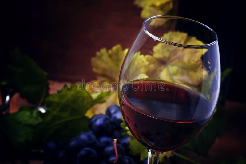 Czerwone wino od gronowego rozmaitości merlot w szkle, roczników drewniani półdupki zdjęcia stock