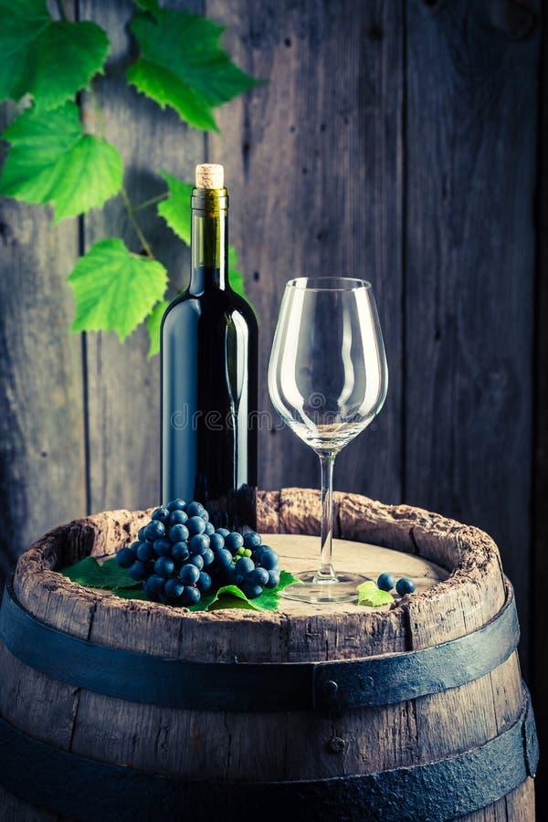 Czerwone wino, pusty szkło i winogrona na baryłce, obrazy royalty free