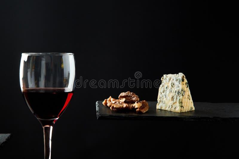 Czerwone wino w krystalicznym szkle obok kawałków ser i orzech włoski na czarnym tle obraz royalty free