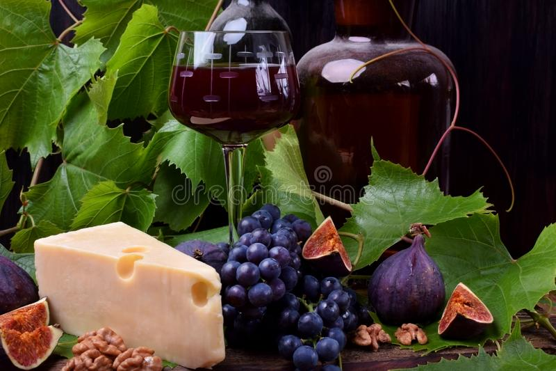 Czerwone wino w szkle otaczającym przekąskami: Maasdam ser, figi, orzechy włoscy i wiązka Isabella winogrona, zdjęcie stock