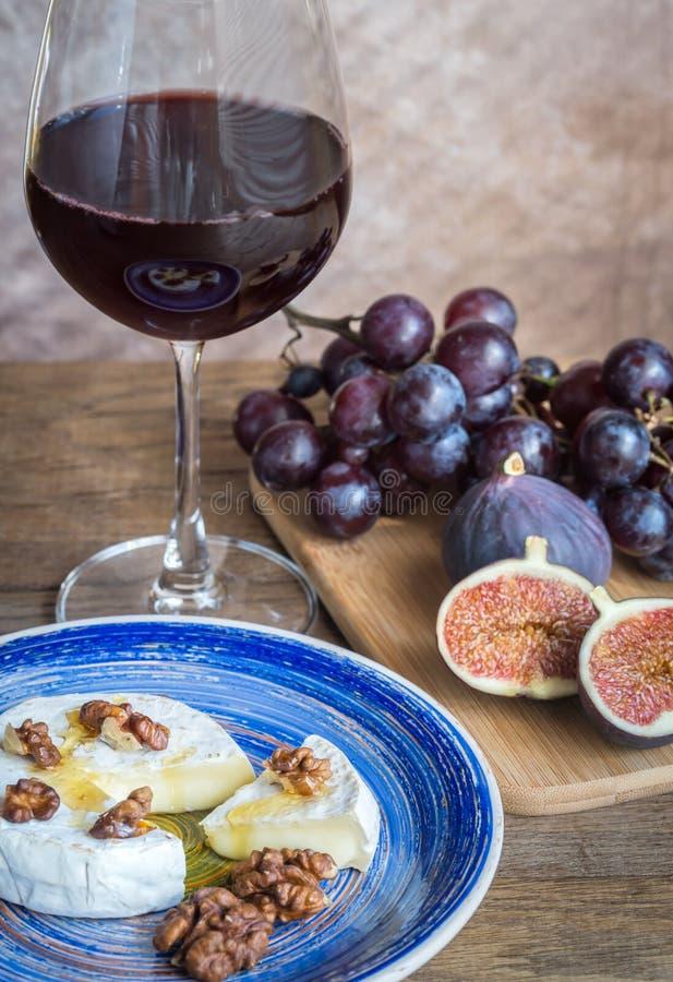 Czerwone wino z camembert, figami i winogronami, obraz royalty free