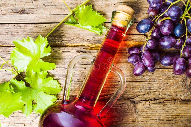 Czerwone wino z winogronem na nieociosanym drewnianym tle zdjęcia stock