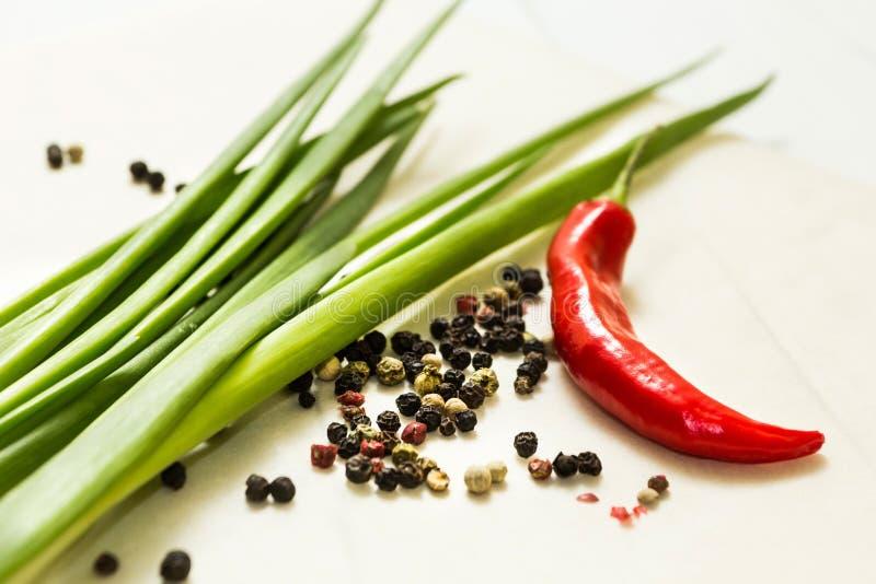Czerwonego chili pieprz i zielona cebula z pikantność na białym drewnianym tle obraz royalty free