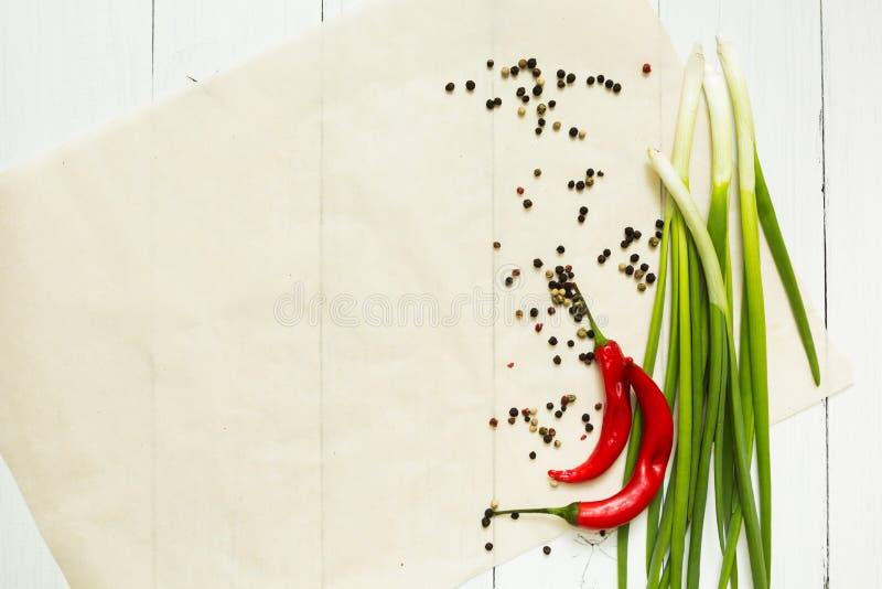 Czerwonego chili pieprz i zielona cebula z pikantność na białym drewnianym tle, odgórny widok Przestrzeń dla naczynia na talerzu  obraz royalty free