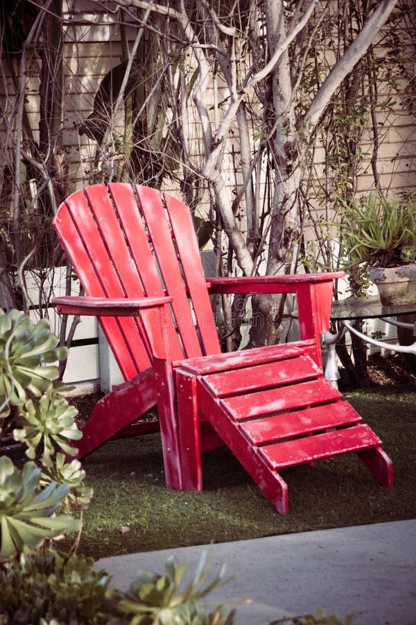 Czerwonego drewnianego rocznika plażowy krzesło w ogródzie fotografia stock