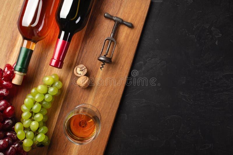 Czerwonego i bia?ego wina butelki z wi?zk?, wineglass na drewnianej desce i czarnym tle obraz royalty free