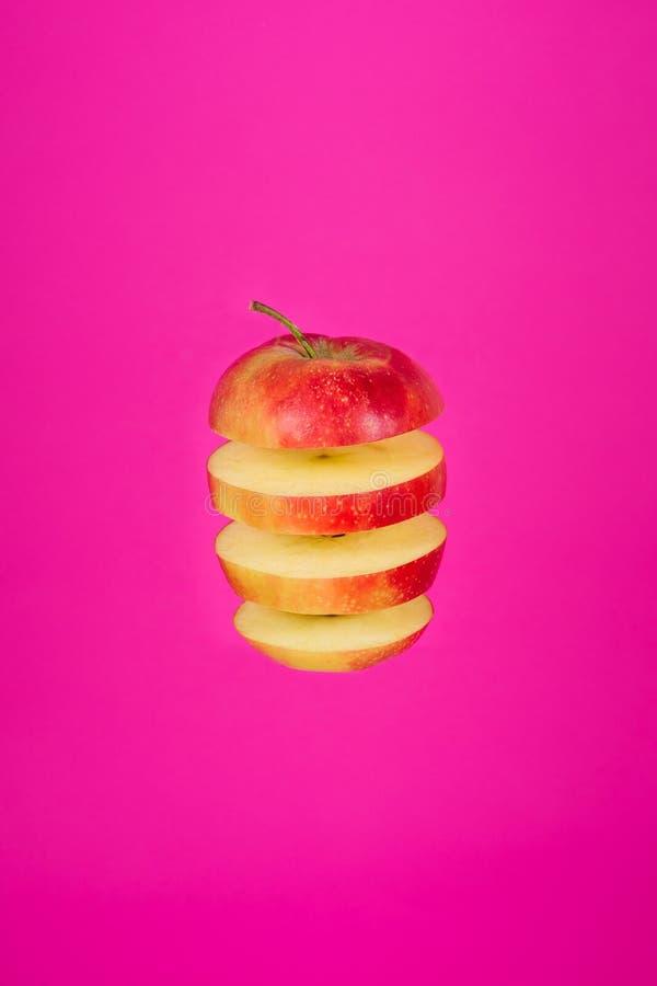 Czerwonego Jabłczanego plasterka Odosobniony latanie na Różowym tle fotografia stock