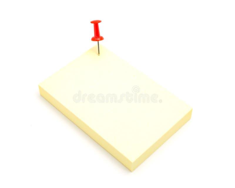 Czerwonego koloru pchnięcia szpilka i żółta kleista notatka na odosobnionym bielu plecy zdjęcia stock