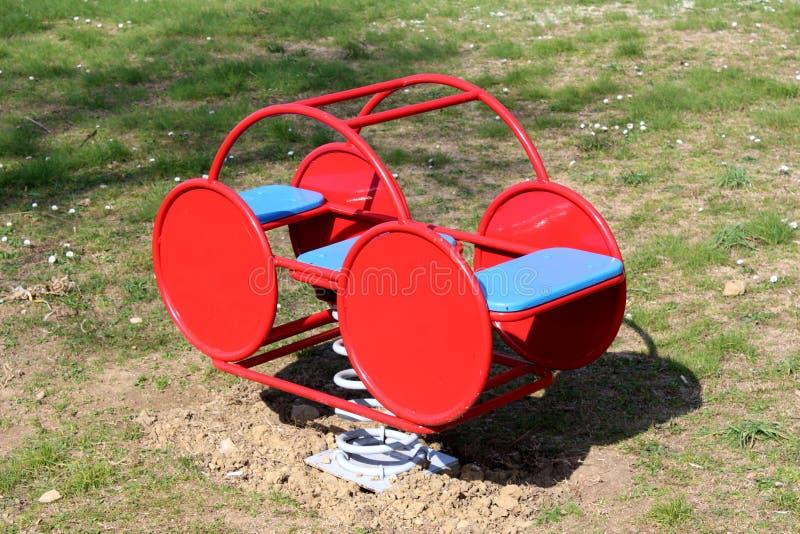 Czerwonego metalu boiska plenerowy jawny wyposażenie w kształcie retro rocznika wiosny przyglądający samochodowy jeździec z dwa s zdjęcie stock