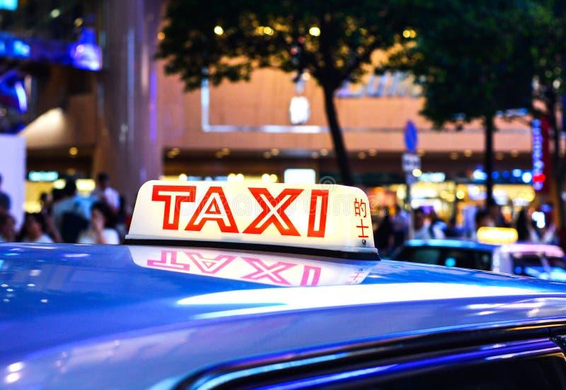 Czerwonego wierzchołka znak Hong Kong taxi przy Ruchliwie Centrum Miasta zdjęcia stock