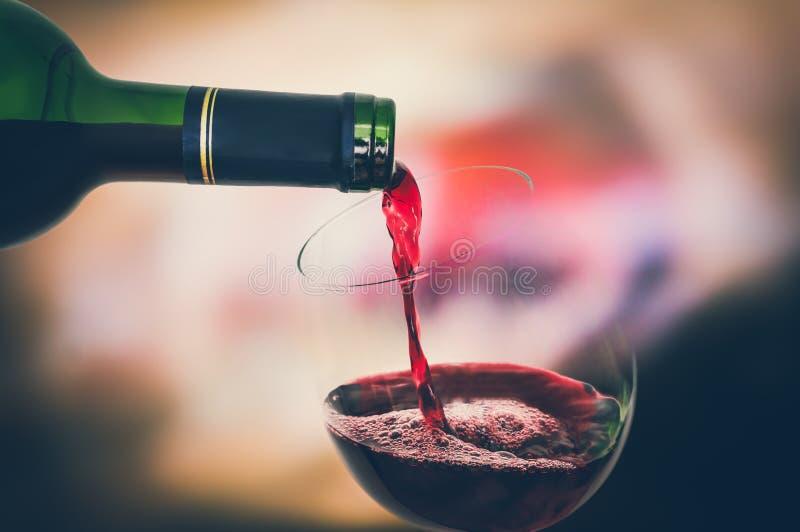 Czerwonego wina dolewanie w wina szkło - świętowania pojęcie obrazy royalty free
