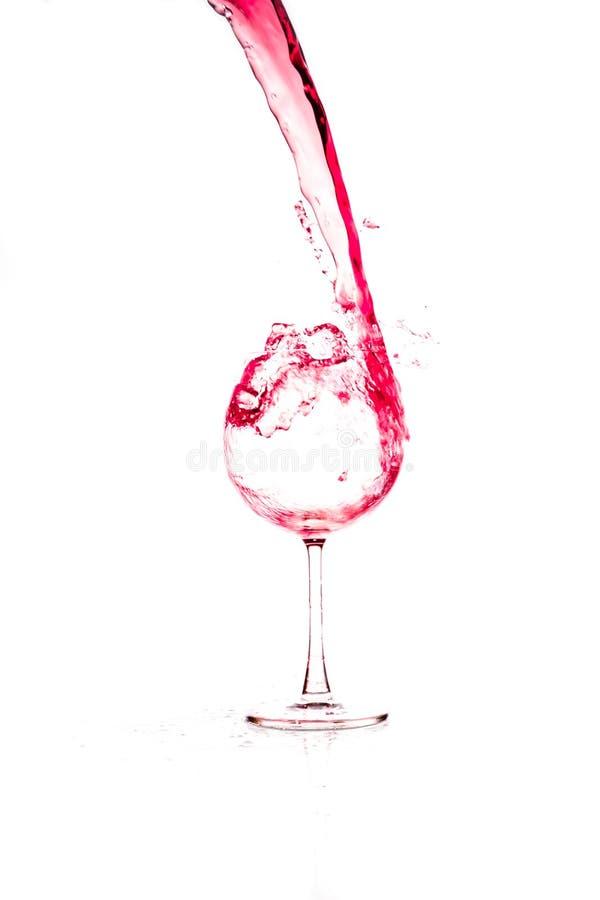 Czerwonego wina dolewanie w wina szkło na białym tle zdjęcia royalty free