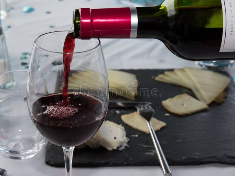 Czerwonego wina dolewanie w wina szkło z serem, zdjęcie stock