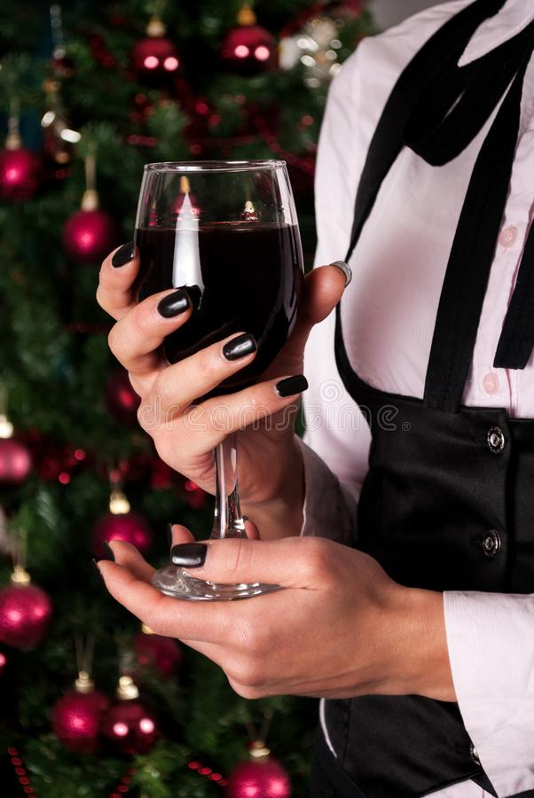 Czerwonego wina szkło w dziewczyn rękach w eleganckiej sukni z krawatem i choinką w tle obrazy royalty free