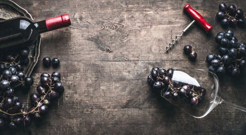 Czerwonego wina tło z butelką, corkscrew, winogrona i wina szkło na ciemnym roczniku drewnianym, obrazy stock