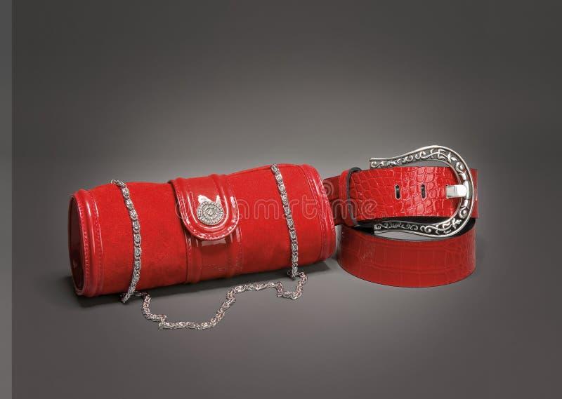 Czerwonego zamszowy rzemienna kiesa i beld na gradientowym szarym tle fotografia royalty free