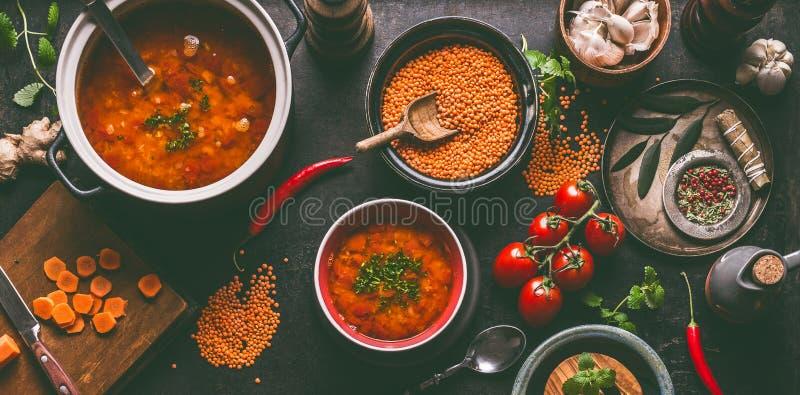 Czerwonej soczewicy polewka z kulinarnymi składnikami na ciemnym nieociosanym kuchennego stołu tle, odgórny widok Zdrowy weganinu obrazy royalty free