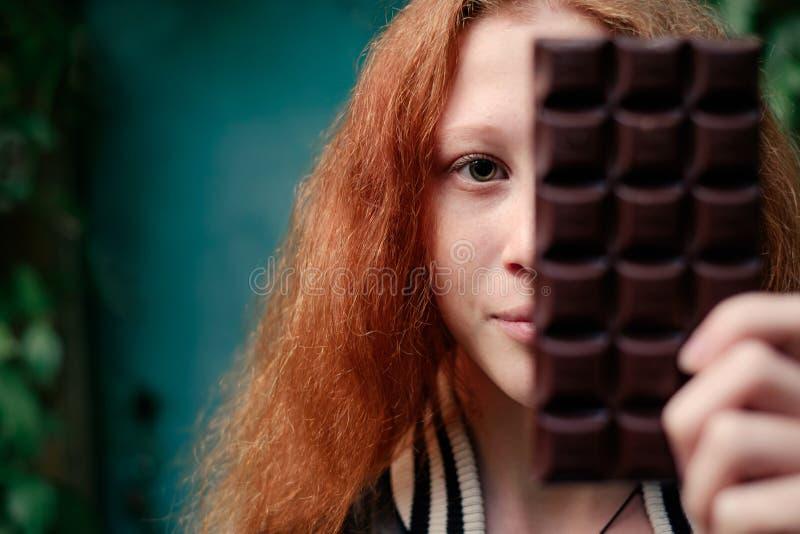 Czerwonej z włosami dziewczyny kryjówki przyrodnia twarz nad smakowitym czekoladowym barem obraz stock