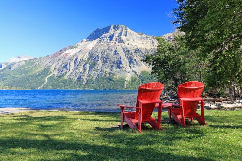 Czerwoni Adirondack krzesła przy Waterton jeziorami parki narodowi, Alberta obraz royalty free