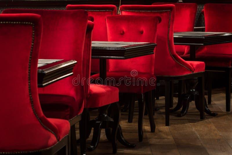 Czerwoni aksamitów krzesła i czerń stoły zdjęcie stock